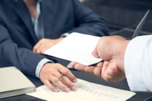 58545540 - hand of a businessman hands over a resignation letter on a wooden table